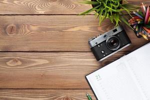tavolo scrivania con macchina fotografica, forniture e fiori foto