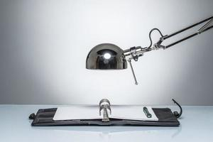 accendendo la scrittura del diario del taccuino con la lampada di scrittorio foto