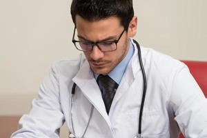 dottore seduto alla scrivania a firmare un contratto foto