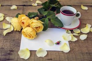 Rose, tazza di caffè e foglio di carta sul tavolo di legno foto