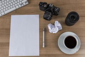 desktop con fotocamera foglio bianco e caffè foto