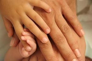 le mani di un bambino genitore e di un bambino uniti tutti insieme foto