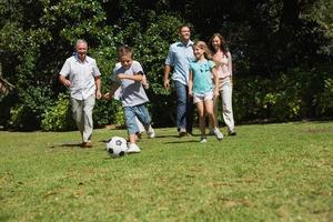 felice famiglia multi-generazione a giocare a calcio
