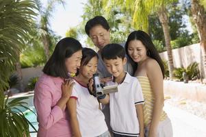 famiglia guardando lo schermo della videocamera foto