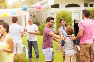 famiglia di diverse generazioni che godono insieme della festa in giardino foto