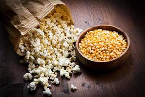 ciotola di popcorn e kernelson un tavolo di legno foto