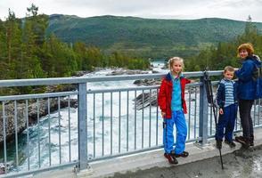 famiglia vicino alle cascate del fiume di montagna (norge) foto