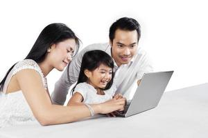 famiglia allegra con il computer portatile in studio foto
