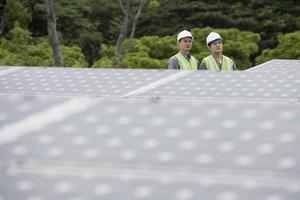 due ingegneri asiatici in una stazione di pannelli solari foto