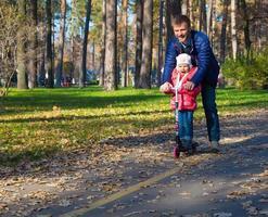 giovane padre e bambino felice cavalcando scooter scooter nel parco