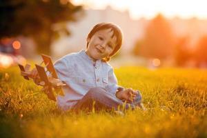 ragazzo carino, giocando con l'aeroplano sul tramonto nel parco foto