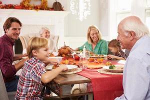 famiglia con i nonni che godono del pasto del ringraziamento al tavolo