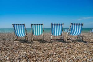 4 sedie a sdraio su una spiaggia di ciottoli foto