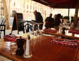tavolo con posate e bicchieri in un caffè di Parigi foto