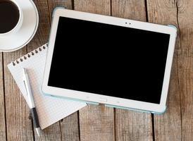 tablet pc vuoto e un caffè e un taccuino con la penna foto