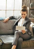 donna d'affari in appartamento loft e l'utilizzo di tablet pc foto