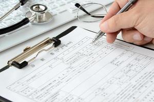 medico che scrive cartella clinica foto