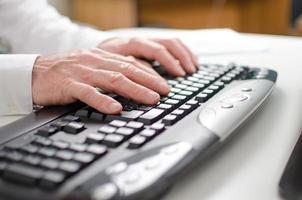 mani che digitano su una tastiera foto