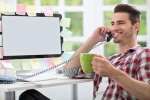uomo sorridente che beve caffè in ufficio foto