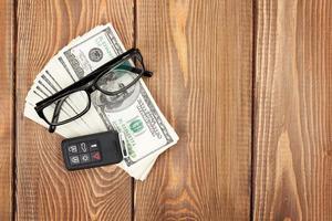 denaro contante, occhiali e chiave a distanza auto sul tavolo di legno foto