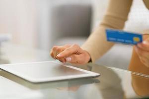 primo piano sulla giovane donna con carta di credito utilizzando tablet pc foto
