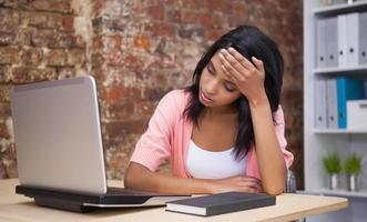 donna travagliata seduto alla sua scrivania con un computer portatile foto