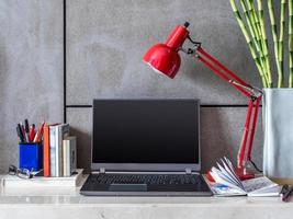 scrivania moderna con computer portatile, lampada e vaso di fiori foto