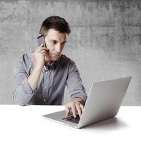 vicino immagine di uomo d'affari multitasking utilizzando un computer portatile foto