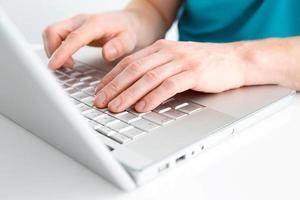 primo piano di digitare mani maschili sulla tastiera foto