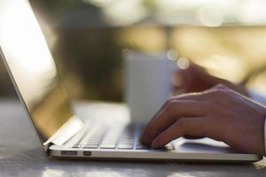 uomo che lavora con il computer portatile e la tazza di caffè all'alba foto