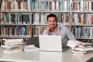 giovane studente che utilizza il suo computer portatile in una biblioteca foto