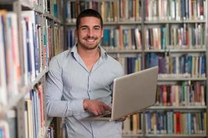 studente maschio felice con il computer portatile in biblioteca foto