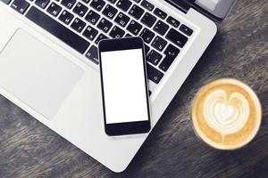 smartphone in bianco sul computer portatile con una tazza di caffè foto
