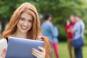 studente grazioso che sorride alla macchina fotografica facendo uso del pc della compressa foto