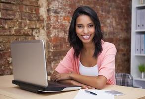 donna felice che per mezzo del suo computer portatile che sorride alla macchina fotografica foto