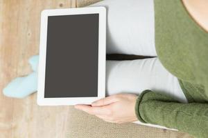 digitabl tablet e mani di donna, a casa seduto sul divano foto