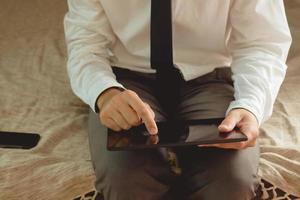 uomo d'affari solo nella camera d'albergo, seduta sul letto foto