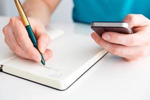 la mano dell'uomo scrive la penna nel diario e tiene in mano mobil foto