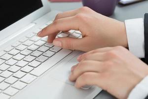 primo piano delle mani della donna che scrivono al computer portatile foto
