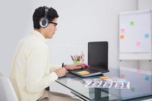 uomo d'affari che gode della musica e che per mezzo del computer portatile foto