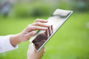 donna che utilizza il pc digitale della compressa nel parco. foto