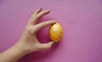 mano umana che tiene un uovo di Pasqua giallo sventato