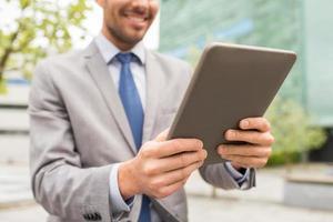 stretta di uomo d'affari con tablet pc in città foto
