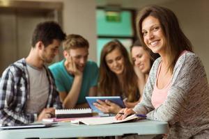 amici sorridenti seduti studiando e utilizzando tablet pc foto