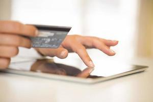 Chiuda in su delle mani della donna facendo uso della compressa digitale foto
