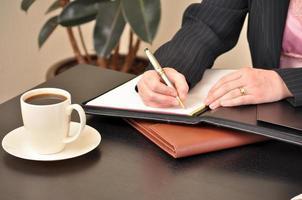 imprenditrice prendendo appunti durante la riunione foto