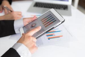 primo piano del gruppo di affari che per mezzo della compressa digitale con Di finanziario foto