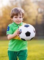 un ragazzo biondo di 4 che gioca a calcio con il campo di calcio onl foto
