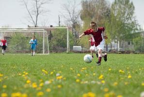 ragazzino che gioca a calcio foto