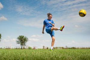 ragazza calciare il pallone da calcio foto